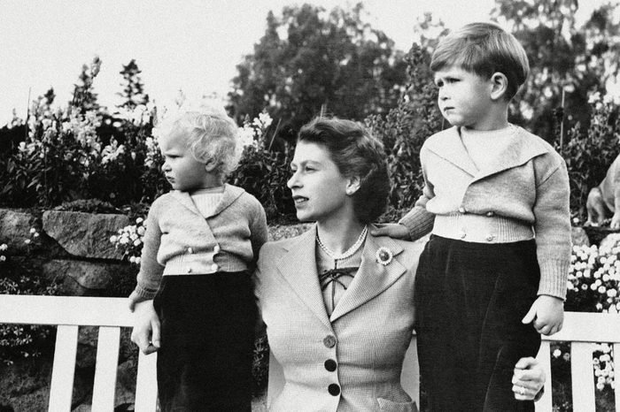 Queen Elizabeth II Prince Charles, four years old, is shown with his mother, Queen Elizabeth II, and sister, Princess Anne, on grounds of Balmoral Castle, Scotland, . Their interest is taken up with frolics of Royal household dogs
