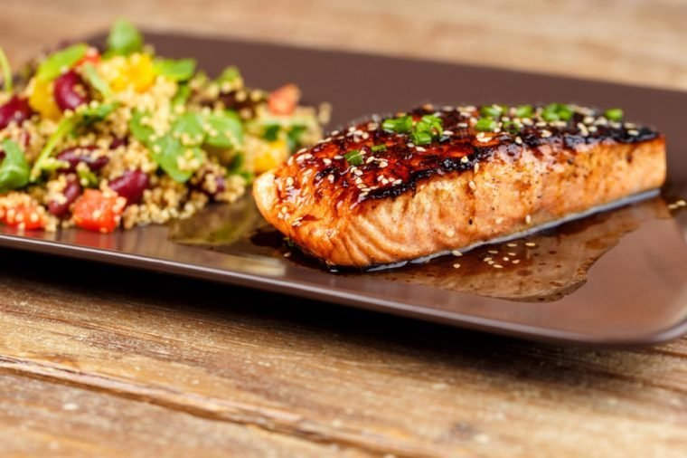 Grilled salmon with quinoa salad on brown plate.