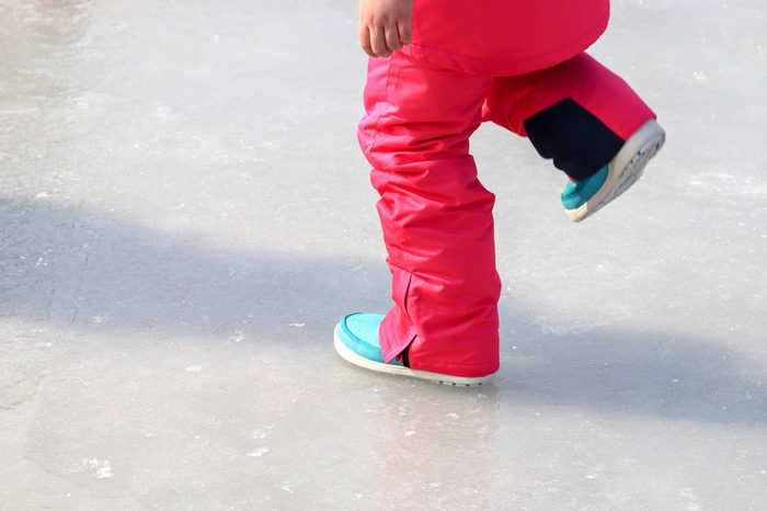 The legs of a girl walking on ice.