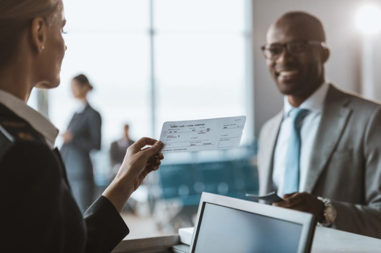 close-up shot of smiling african american businessman giving passport to staff at airport check in counter