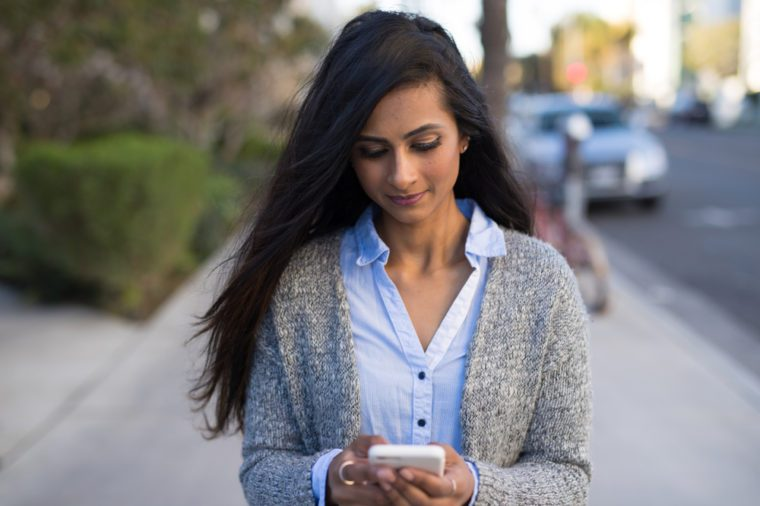 Indian woman in city walking texting cell phone