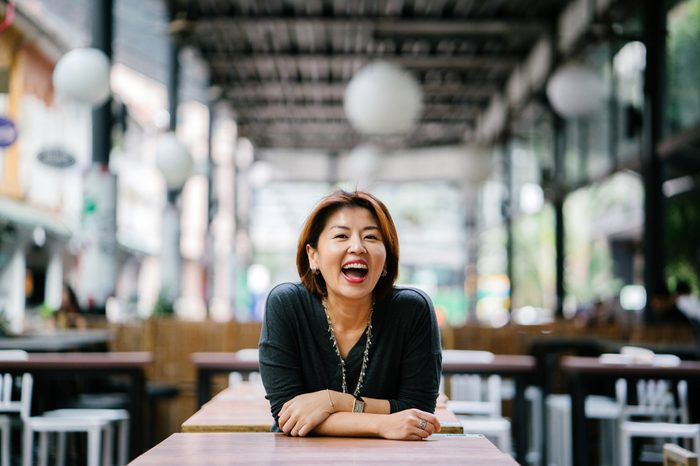Portrait of an elegant mature Asian woman laughing during the day. She's dressed professionally and leaning against a table in a coworking space, cafe or office in Asia.