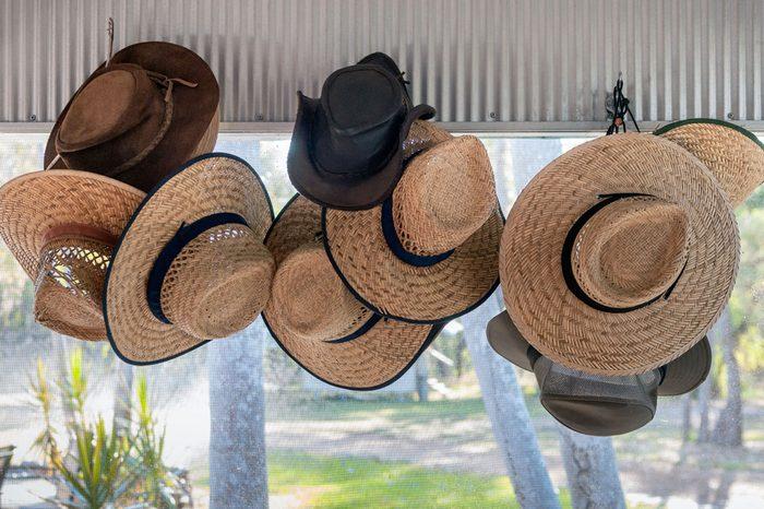 Several safari sun hats hanging at the entrance of a base camp