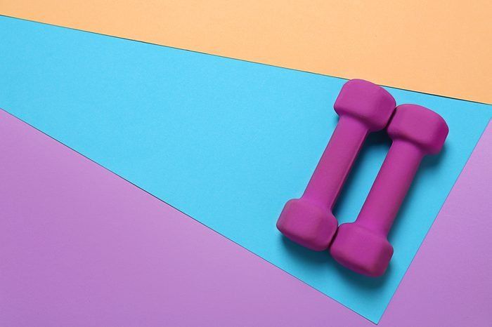 Dumbbells and blank space for exercise plan on color background. Flat lay composition