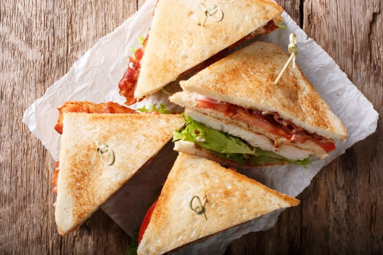 layer club sandwich with turkey meat, bacon, tomatoes and lettuce macro on paper. Horizontal top view from above