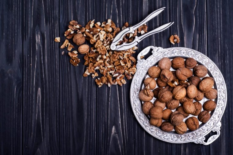 Walnut kernels and whole walnuts on a black wooden background. Top view