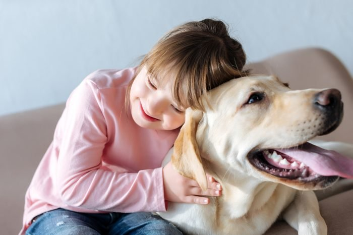Happy child with down syndrome and Labrador retriever dog cuddling on sofa