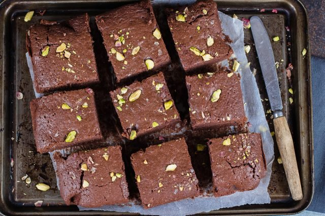 Homemade chocolate brownies with pistachios on dark background. Copy space, top view