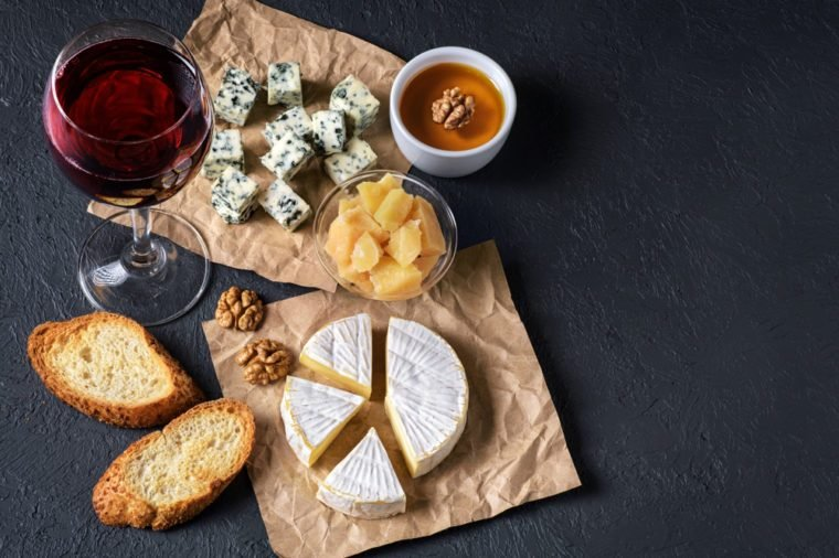 Camembert cheese, blue cheese, parmesan, toasts, honey, walnuts and glass of wine on a dark background. Flat Lay.