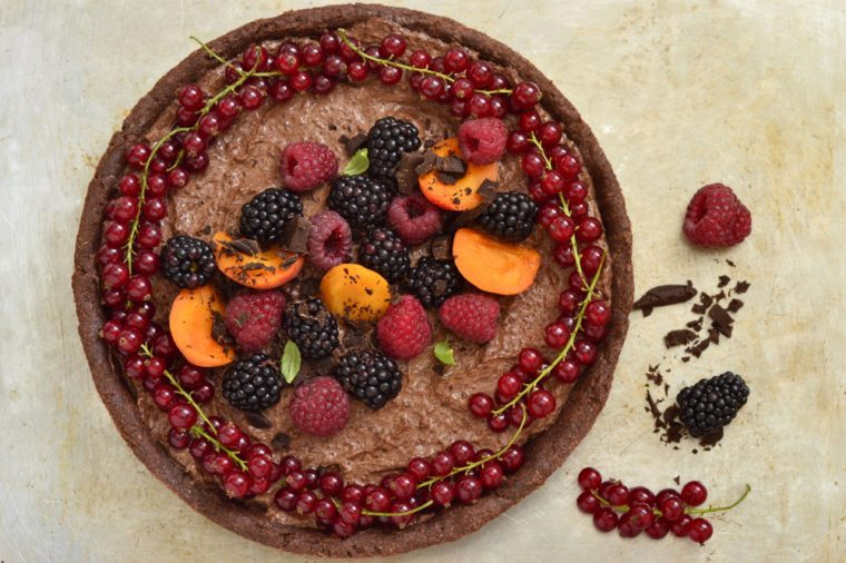 Chocolate tart with chocolate cream and fresh berries, top view