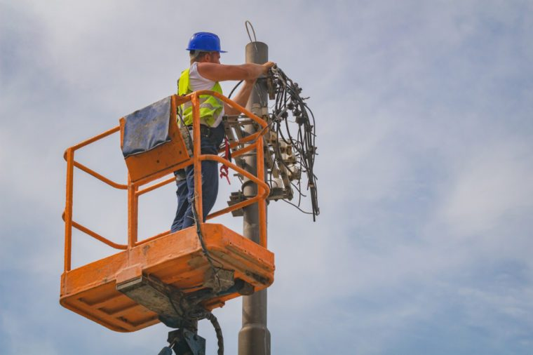 Power line worker fixing from the truck basket.