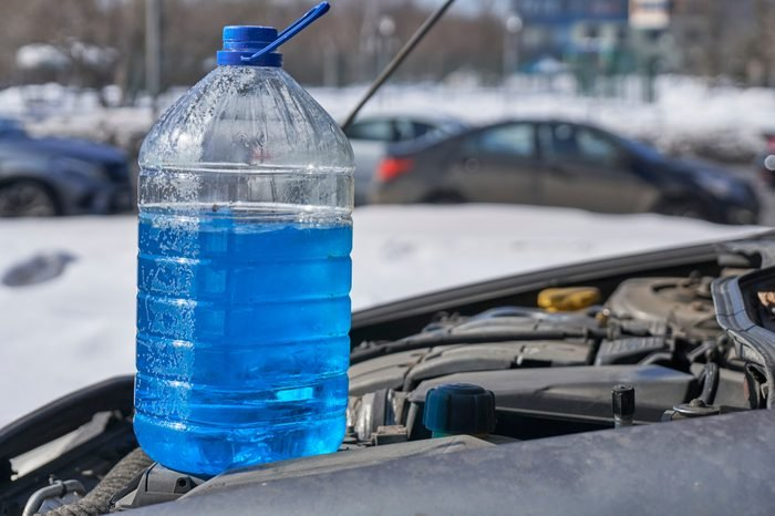 Bottle with non-freezing liquid for windshield washer standing on the engine of a car in front of a road with cars in winter outdoors