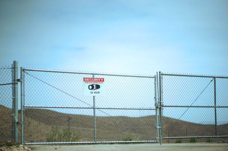 Warning Restricted Area Under Surveillance Sign On Gate