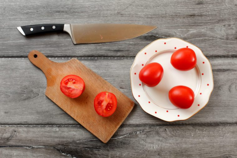 Table top view on three tomatoes on white porcelain plate with red dots, cutting board with tomato cut to half next to it, chef knife also laying on the gray wood desk.