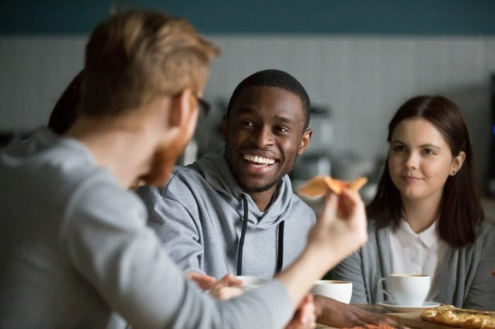 Happy millennial african american man laughing at joke hanging in pizzeria sharing pizza with best friends, smiling attractive black guy having fun talking to buddy sharing lunch at cafe restaurant