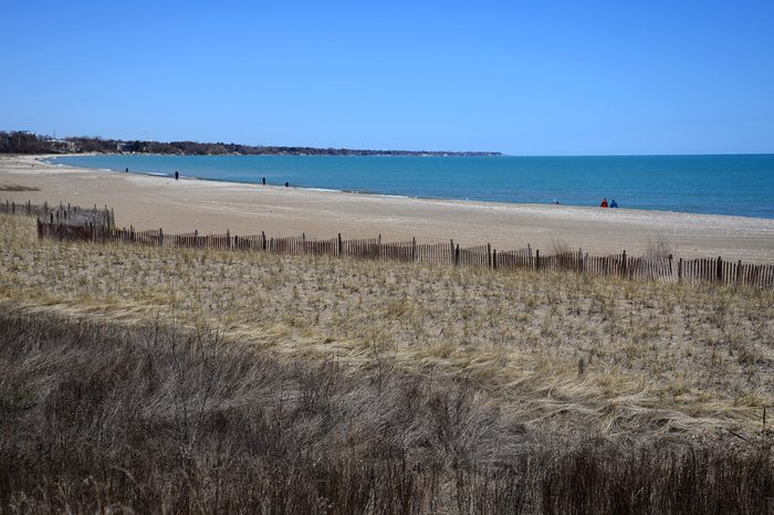 Lake Michigan beach on a cool spring sunny day in Kenosha Wisconsin. Peer north to the Wind Point Lighthouse miles in the distance. Winter wear is still needed on a cold spring day.