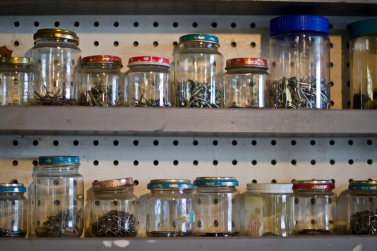 A few shelves full of jars that are filled with different screws and small items