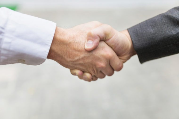 Closeup of two confident business man shaking hands