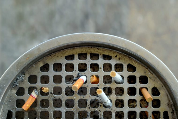 ashtray and cigarette with soft-focus and over light in the background. top view