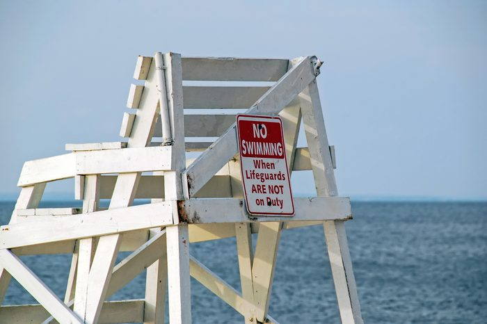 Lifeguard tower on the sandy beach beautiful seascape summer morning. Close-up warning sign