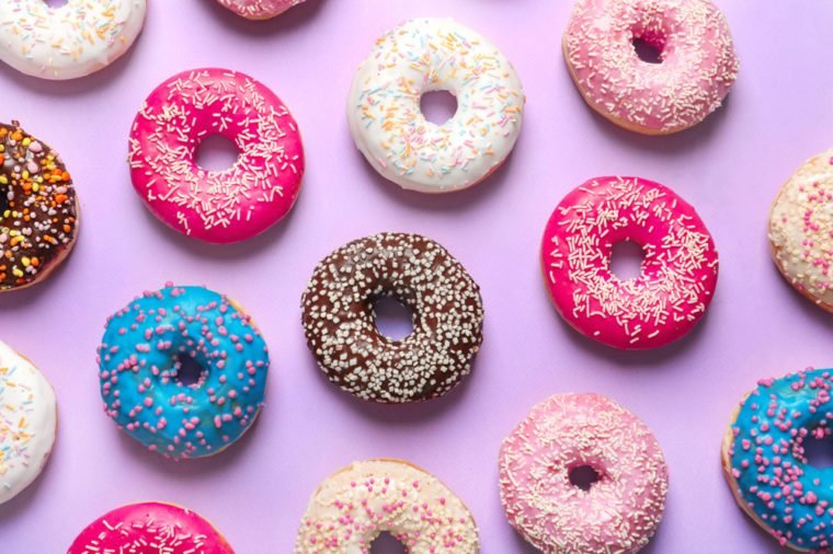 Delicious doughnuts with sprinkles on color background, top view