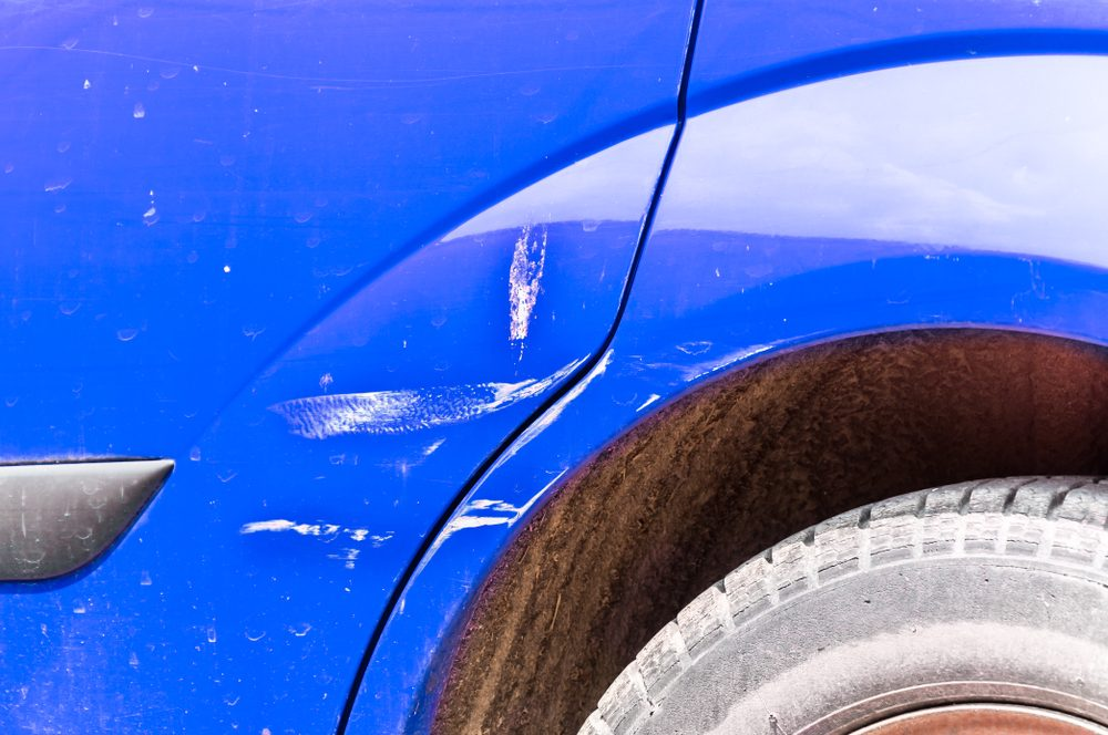 Blue Scratched Car With Damaged Paint In Crash Accident On The Street Or Collision Parking