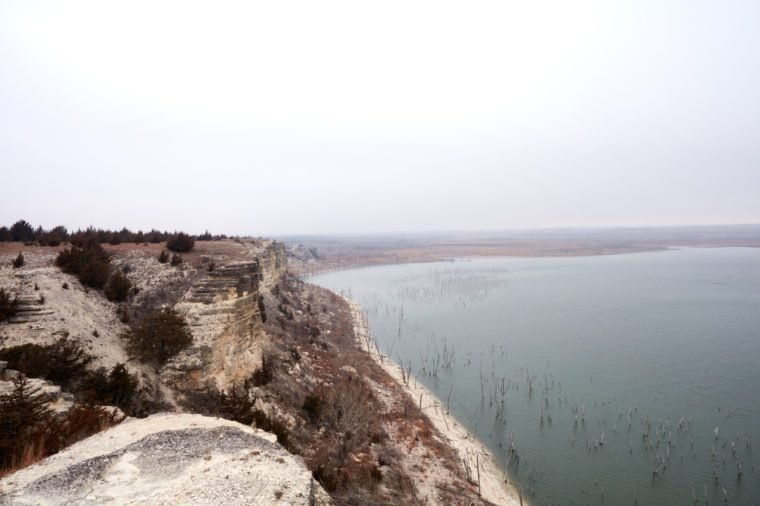 The sandstone cliffs of the Cedar Bluff Reservoir with a view over the dam built for flood control ad irrigation