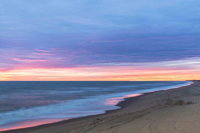 Sunrise along the Atlantic Ocean in Virginia Beach at Little Island Park in Sandbridge. The sun creates pink and purple pastel reflections on the surf