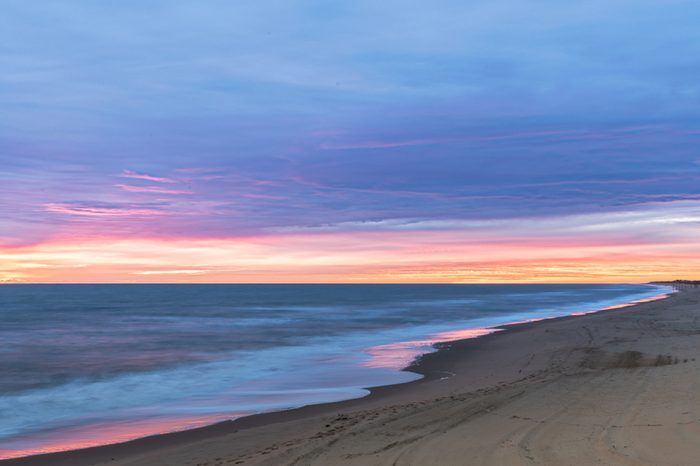 Sunrise along the Atlantic Ocean in Virginia Beach at Little Island Park in Sandbridge. The sun creates pink and purple pastel reflections on the surf