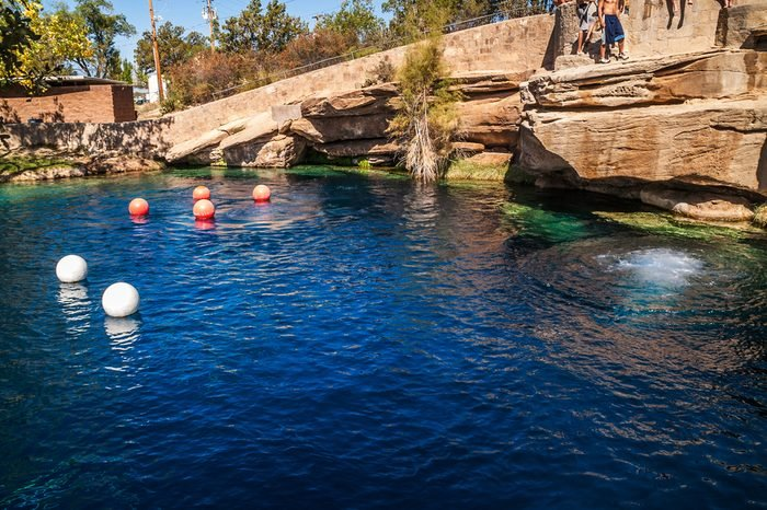 At 80 feet deep with clear blue water, the Blue Hole on Route 66 in Santa Rosa, NM, attracts divers and others. One person just jumped into the pool creating the rings of ripples.