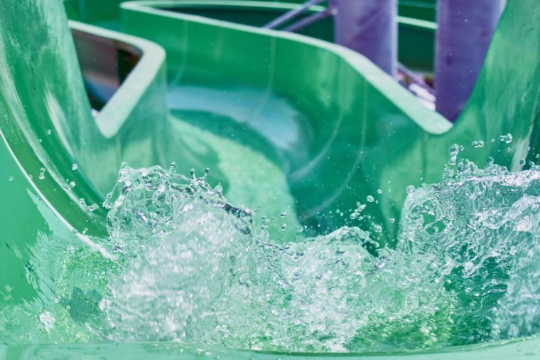 The stream of splashing water on green hill in water park for riding children