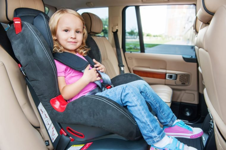 Small girl is sitting in child cat seat, looking at the camera