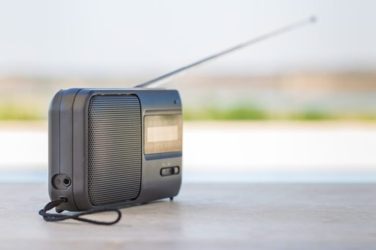 A small transistor radio with a string cord handle outside.
