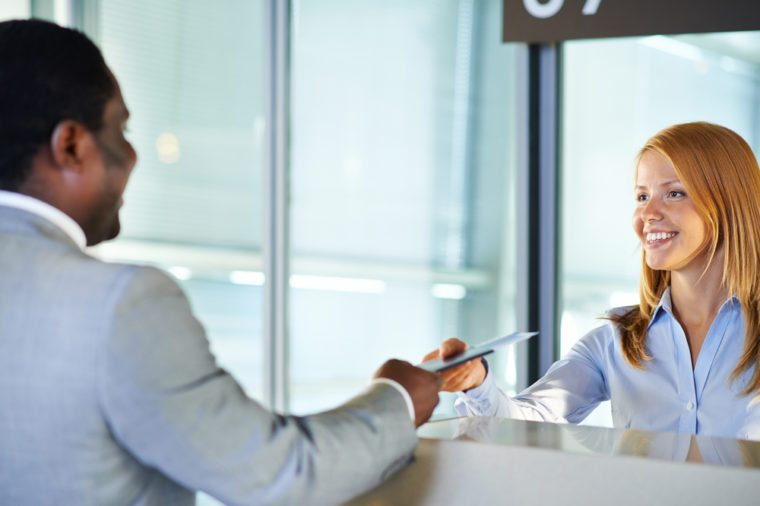 Friendly woman giving passport and ticket back to businessman at airport check-in counter