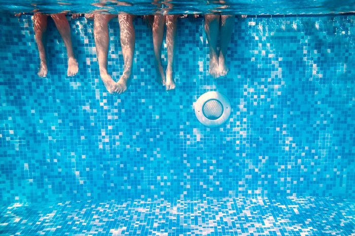 Children's and adults legs underwater in the swimming pool