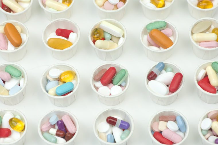 Many different assorted colorful pills in paper medication dosage cups.