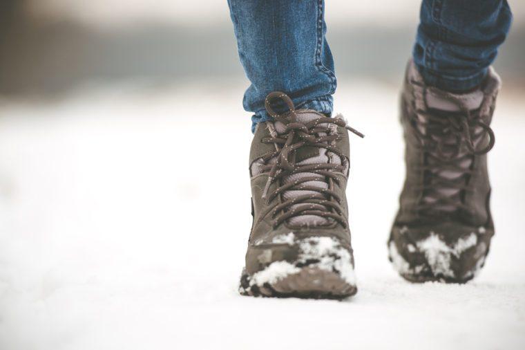 girl in winter boots walking on snowy road