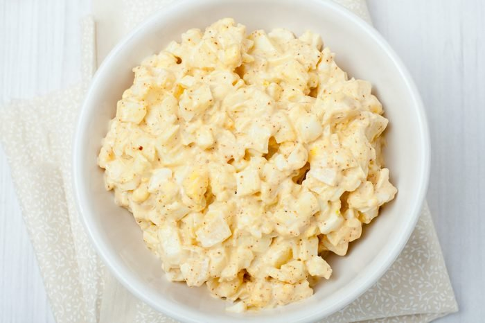 homemade egg salad in white bowl on white background, top view