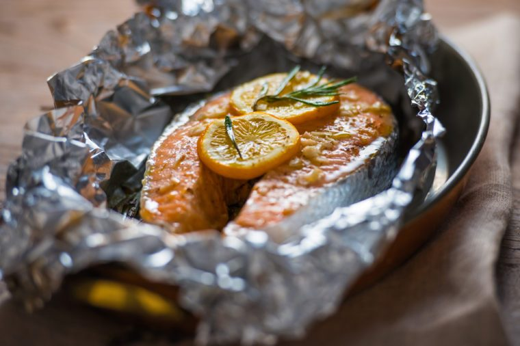 Salmon steak baked with lemon and herbs in foil
