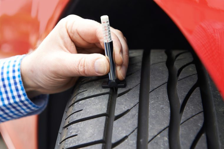 Close-Up Of Man Checking Tread On Car Tyre With Gauge