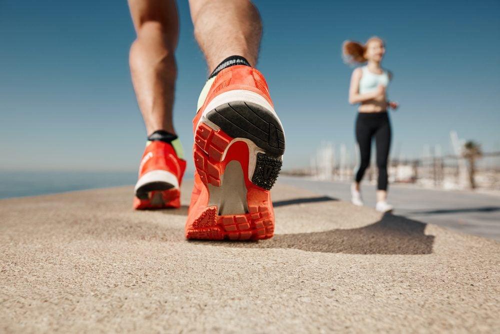 Runner feet running on road closeup on shoe. Sportsman fitness sunrise jog workout welness concept.