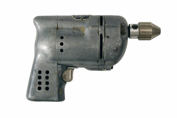 A battered vintage steel power tool isolated on a white background