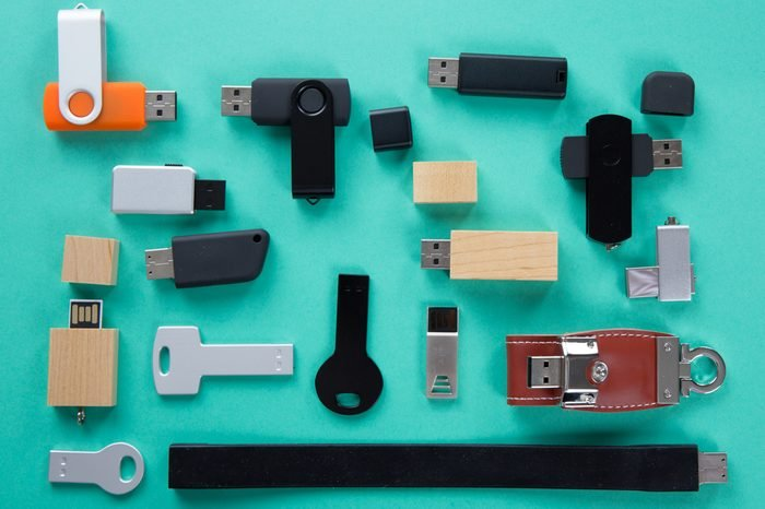 Row of color USB flash drives on green background