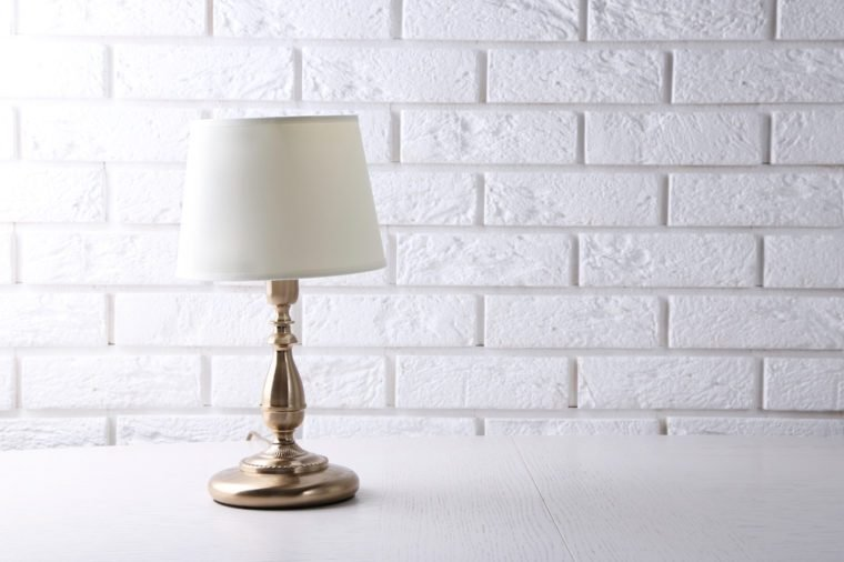 Old fashion table lamp on table on brick wall background