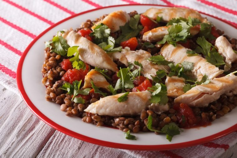 breakfast of brown lentils with grilled chicken and herbs close up on a plate. horizontal