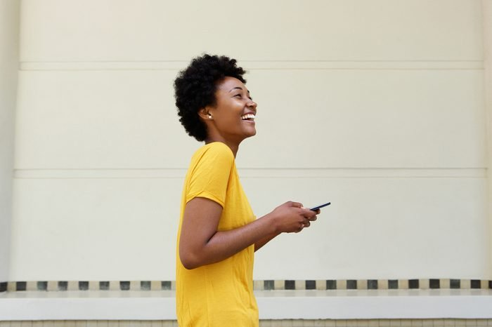 Side portrait of cheerful young african woman walking with a mobile phone