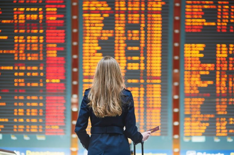 Young woman in international airport looking at the flight information board, holding passport in her hand, checking her flight