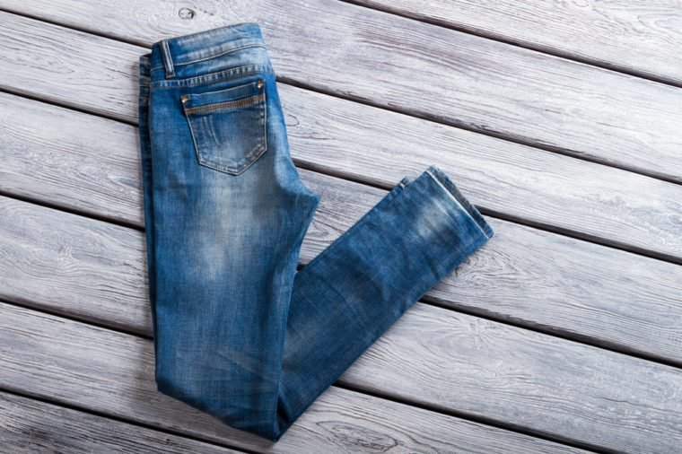 Folded blue jeans. Denim pants on wooden background. Woman's new casual jeans. Last item at special price.