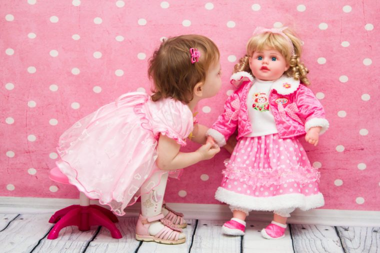 little girl on a pink background playing with a doll