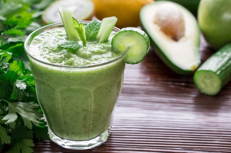 Left glass of green vegetable smoothie near ingredients celery, avocado, cucumber, apple, kiwi and herbs, right empty space on wooden background. Green vegetable smoothie and ingredients. Horizontal.